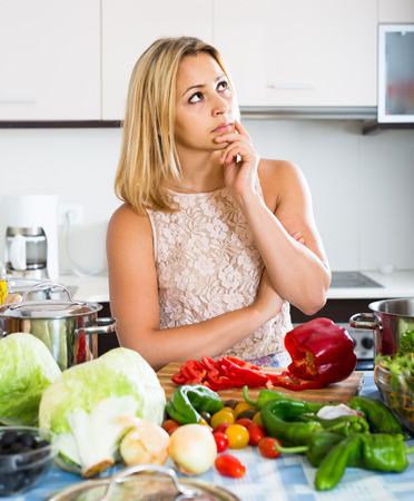 in low spirits: Tired young spanish woman leaning her elbows at the kitchen