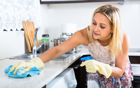domestic chore: Young housewife wearing rubber gloves is using cleaner in a spray bottle to clean kitchen Stock Photo