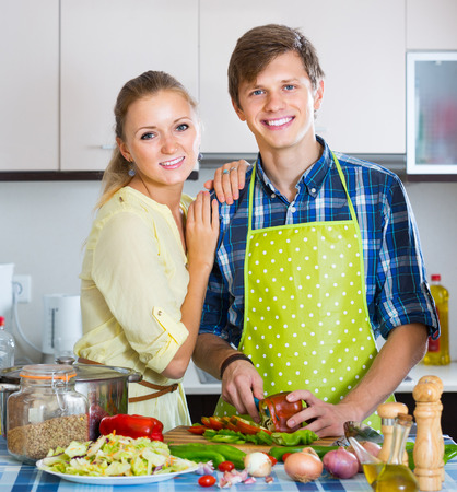russian man: smiling russian man and woman standing near table  in domestic kitchen