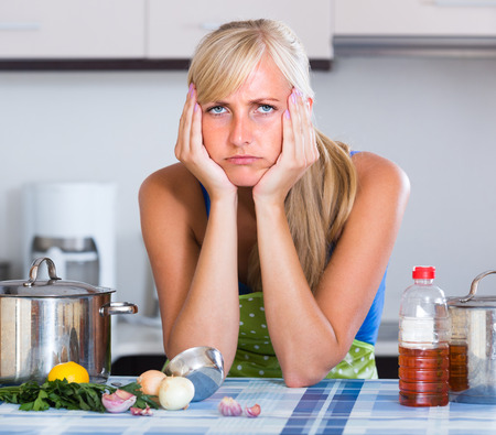 anguish: Young nervous woman thinking of problems in home kitchen