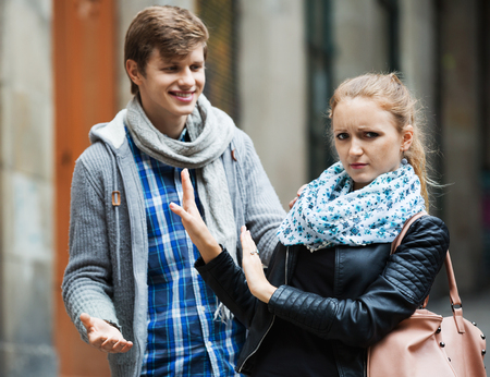 accosting: Public harassment: annoying  man chasing  irritated  beautiful european girl Stock Photo