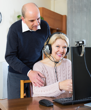 global retirement: Happy elderly couple talking with someone online and smiling Stock Photo