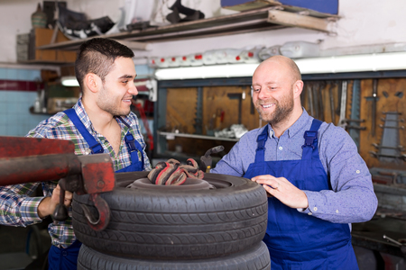 mounting: Smiling adult mounting specialists in coveralls working at auto repair shop. Focus on the right man
