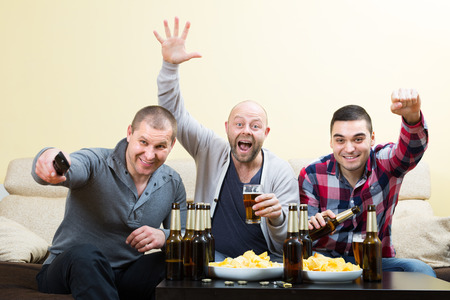 watching football: Three excited male friends drinking beer and watching football game at home Stock Photo