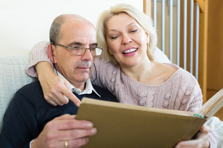 satisfied people: Portrait of happy senior spouses smiling with picture album at home. Focus on woman
