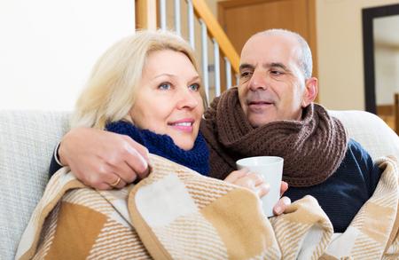 spouses: Elderly loving spouses under blanket drinking tea on couch