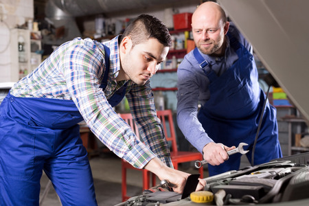 mounting holes: male mounting specialists working at auto repair shop.