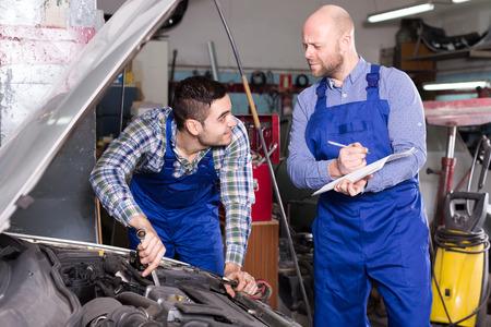 personas ayudando: Mecánico en un taller de reparación ayuda a agente de seguros para calcular la pérdida de Foto de archivo