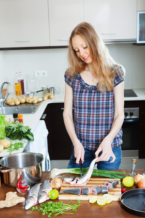 fryingpan: Long-haired housewife cooking saltwater fish at domectic kitchen