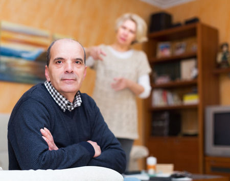 adultery: Family quarrel. Unhappy elderly man with angry wife at home Stock Photo