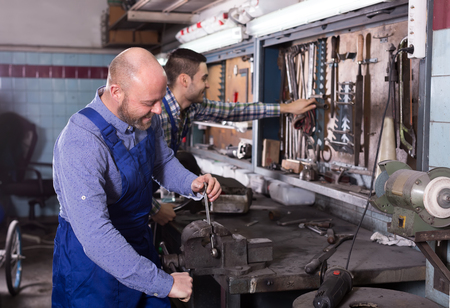 toiling: Two positive mechanics at work in a repair shop Stock Photo