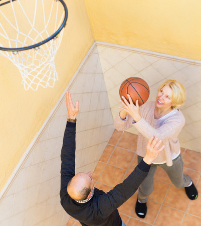 spouses: Happy activity elderly spouses throwing the ball into basket Stock Photo