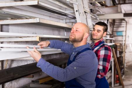toolroom: Workem in blue uniform are choosing PVC window profiles from a rack