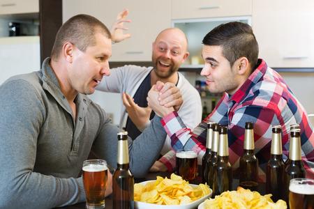 borracho: Sonrisa y hombres adultos ebrios armwrestling, su amigo de apoyo