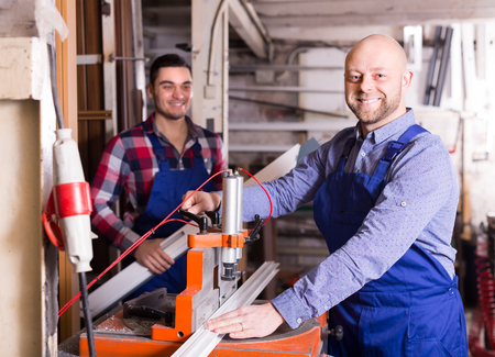 toolroom: Two happy smiling workmen in uniform working on a machine in PVC shop Stock Photo