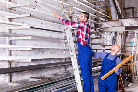 enginery: Couple of workmen on step-ladder inspecting window frames at factory