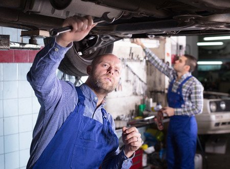 serviceman: Professional concentrated serviceman  repairing car of client