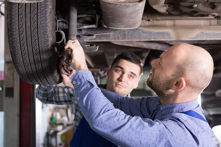 Two serious car mechanics checking up pressure in tires at garage Stock Photo