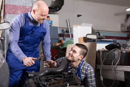 two car garage: Portrait of two smiling professional car mechanics working together at garage