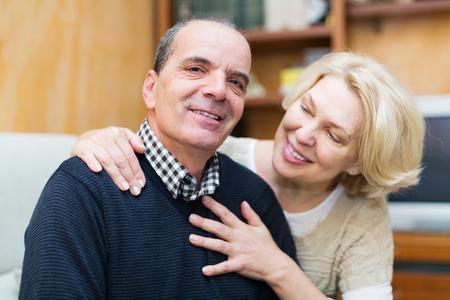 sofa: Indoor portrait of happy loving mature couple