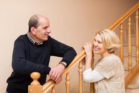 spouses: Smiling senior spouses leaning against stairway indoor