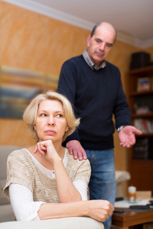 Angry senior mature woman and man after quarrel at home. Focus on woman