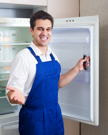refrigerator kitchen: Happy adult handyman repairing refrigerator in domestic kitchen Stock Photo