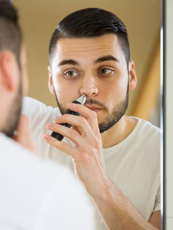 nariz: quitar el pelo masculina de la nariz y las orejas con corta Foto de archivo