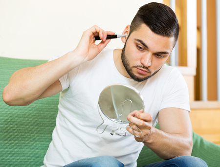 nose: handsome young man trims nose and ears hair at home Stock Photo