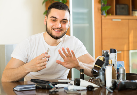 positiv: Handsome smiling young guy cutting nails with cuticle scissors Stock Photo