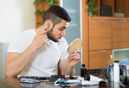 trimmer: Handsome guy using trimmer for removing hair in his ear