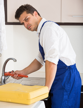 blue overall: Serious plumber in blue overall working in domestic kitchen