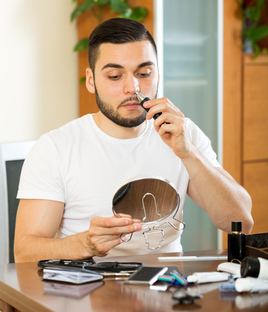 trims: Adult beautiful man trims nose and ears hair at home