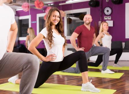 estudiantes adultos: Adultos sonrientes felices que tienen un grupo de clases de fitness en el club de deporte