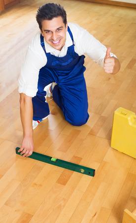 floor level: Professional builder checking floor with spirit level indoors