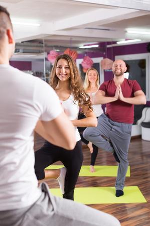 adult learners: Entrenador mostrando a adulto Estudiantes nueva postura de yoga en el interior