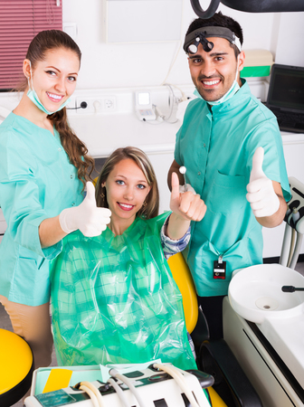 operative: Portrait of cheerful smiling female patient and dentist with assistant at dental clinic Stock Photo
