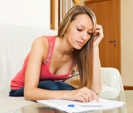 Thoughtful young female student is preparing for exam at home with documents and notes