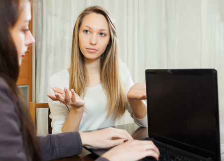 intercommunication: woman talking with employee with notebook  in interior of home or office