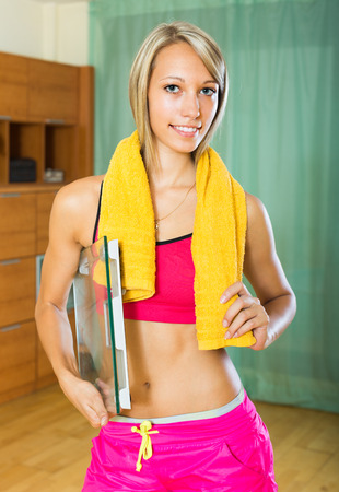house trained: Smiling slender figured girl with scales and towel indoor