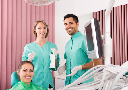 an operative: Portrait of  smiling dentist and positive patient at dental clinic