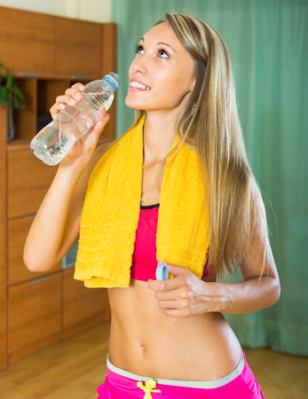 house trained: Smiling girl with towel and bottle of water at home after training Stock Photo