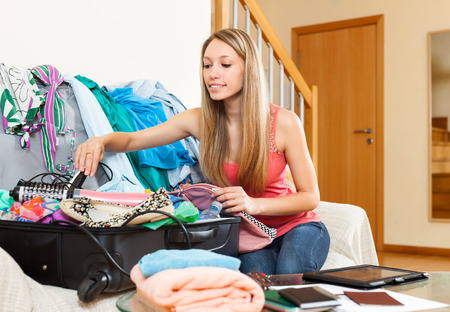 open suitcase: Happy woman sitting on the couch and putting things in an open suitcase