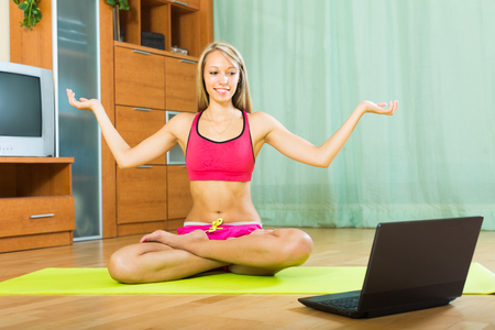 house trained: Happy girl doing yoga with laptop at home and smiling