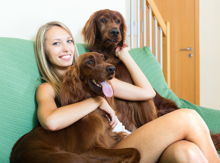 irish woman: Young woman hugging two red Irish setters and smiling.Focus on dog Stock Photo