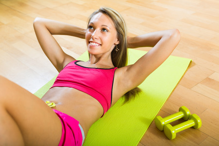 house trained: Happy smiling young woman working out on exercise mat at home