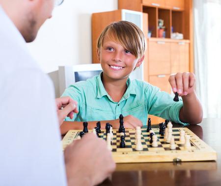 chess: Padre e hijo feliz juego de ajedrez que gana en el interior Foto de archivo
