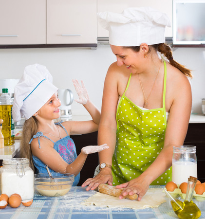 little dough: Cheerful little girl helping mother to make a dough Stock Photo