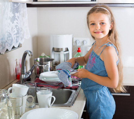 unwashed: Cheerful russian female child cleaning dishware at home
