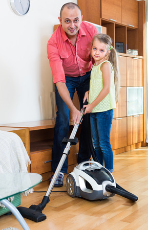 teaching adult: Smiling adult man teaching little daughter vacuuming during clean-up Stock Photo